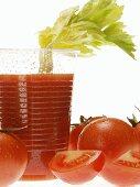 Tomato juice in plastic tumbler with celery; tomatoes