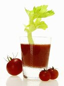 Tomato juice in glass with celery; cherry tomatoes