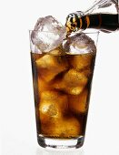 Pouring Cola into glass with ice cubes