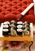 Maki-sushi platter in front of red cushion