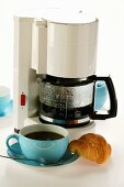 Coffee machine, blue coffee cups and croissant