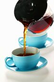 Pouring coffee out of glass coffee pot into blue cup