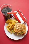 Cheeseburger, bites taken, with chips and Cola