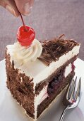 Decorating a piece of Black Forest gateau with cherry