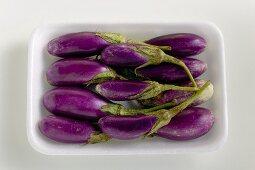 Baby aubergines in white dish