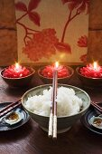 Bowl of rice in front of burning candles (Thailand)