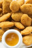 Many chicken nuggets with apricot sauce on plate