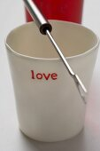 Beaker with the word 'love' and fondue fork