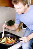 Young man stir-fying vegetables