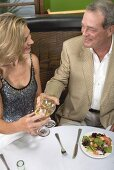 Man & women clinking glasses of wine in restaurant