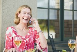 Blond woman on phone sitting at laid table on a terrace