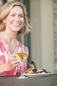 Blond woman at table with salad and wine