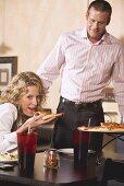 Frau im Restaurant isst Pizza, Mann kommt dazu