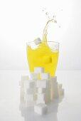 Orangeade with sugar cubes, splashing out of glass