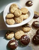 Chocolate-dipped & -coated oat biscuits on heart-shaped plate