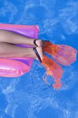 Feet in flippers on an airbed in water