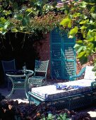 Table, chairs and lounger under canopy of leaves