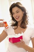 Woman with perfume in gift wrappings