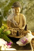 Buddha statue, orchid flowers and incense cones