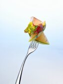 Melon, lettuce and ham on a fork
