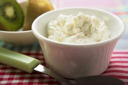 Cottage cheese in a small bowl, kiwi fruit behind