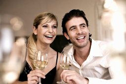 Laughing young couple with white wine glasses in their hands