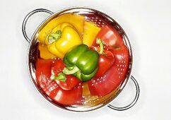 Four peppers (red, yellow, green) in a colander