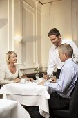 Waiter serving a mature married couple in a restaurant