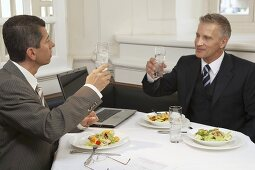 Two men drinking glasses of water during a business meal