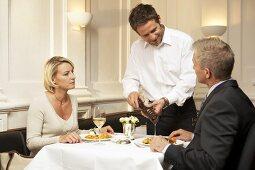 Waiter seasoning a man's food in a restaurant