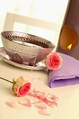 Tea in silver cup and saucer with roses, aroma lamp