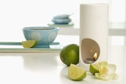 Aroma lamp with limes and orchid flower, bowl of tea