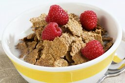 Cereal flakes with milk and raspberries in a bowl