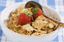 Bowl of wholemeal cornflakes and fresh strawberries