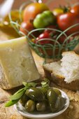 Tomatoes in wire basket, olives, cheese, bread & olive oil