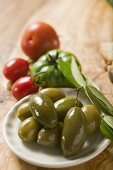 Green olives on plate, a few tomatoes behind
