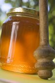 Jar of honey with honey dipper on table in the open air