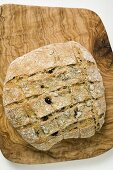 Crusty olive bread on chopping board (overhead view)