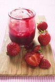 Glas Erdbeermarmelade und frische Erdbeeren auf Schneidebrett