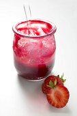 Glas Erdbeermarmelade mit Löffel, daneben frische Erdbeeren