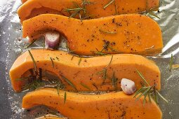 Pumpkin slices with rosemary and garlic on aluminium foil