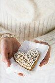 Hands holding gingerbread heart on napkin (Christmassy)