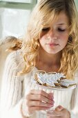 Blond girl holding glass bowl of assorted gingerbread biscuits