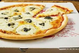 American-style three cheese pizza on pizza box