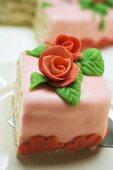 Stück Geburtstagstorte mit Marzipanrosen auf Kuchenheber