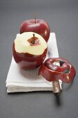 Two red apples, variety Stark, one half-peeled