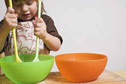 Child stirring bowl with two wooden spoons