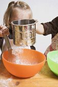 Two children baking (sieving flour into bowl)