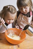 Two children baking (pouring milk into bowl)