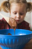 Chocolate icing running from wooden spoon, child in background
